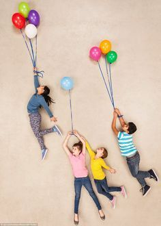 The helium in these balloons must be pretty strong as it\'s making the children float up into the sky