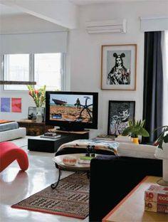 """Integrar para aumentar: """"Subdividir um apartamento pequeno é viver sempre em ambientes apertados"""", acredita o arquiteto Paulo Castellotti. Por morar sozinho e não ter de se preocupar com a privacidade, ele optou por derrubar a parede entre a sala e o quarto. Apoio versátil: o móvel da TV tem uma base giratória que permite virar a tela tanto para a sala como para a cama. Localizado onde antes havia uma parede, também ajuda a delimitar a área do quarto. Uma serigrafia do grafiteiro Ozi (no…"""