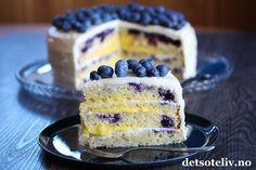 Heisan! Her kommer en ny, herlig festkake. Vi er jo midt i festkakesesongen, så da er det jo bare å kjøre på med festkaker..  Nå må det jo sies at jeg lagde denne kaken på en helt vanlig helgedag uten at det var noen festlig anledning, så det går også an.. Kaken består av myke, lyse kakebunner, som gjør at blåbærene skaper en stilig fargekontrast. Jeg har fylt kaken med ostekrem og hjemmelaget sitronkrem (lemon curd), og så dekket hele kaken med ostekrem og pyntet med masse blåbær. Vakker…