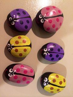 Pastel lady bugs painted on rocks. By Linda Hallett