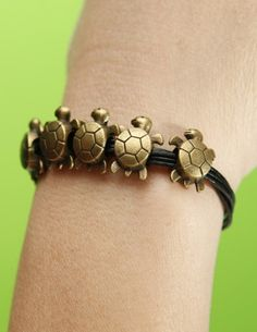 Handmade bronze five longevity turtles bracelet,six black leather cord bracelet.  via Etsy.