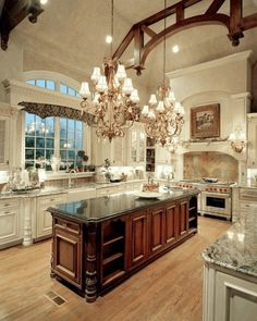 wow...could this kitchen be any more grand?!  love the beams, fancy chandeliers and countertops