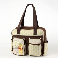 This large double-handle diaper bag features Pooh and a tree embroidered on beige with an all-over forest pattern and brown accents.