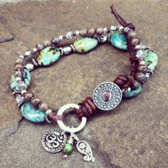 Knotted double strand wrap bracelet with African turquoise and brown snowflake jasper gemstones, silver czech glass beads, and silver-plated spacer accents with a scroll button closure. Antique pewter OM and paisley charms and wire-wrapped turquoise drop. Adjustable. www.facebook.com/kyaracreations