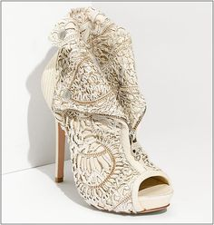 Alexander McQueen light-colored leather booties are topped with an incredibly intricate laser-cut lace   overlay