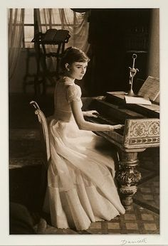 Audrey Hepburn playing a harpsichord.