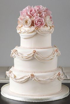 Beautiful traditional wedding cake with draping pearl detail and a lovely shade of lilac flowers for the topper. ᘡղbᘠ