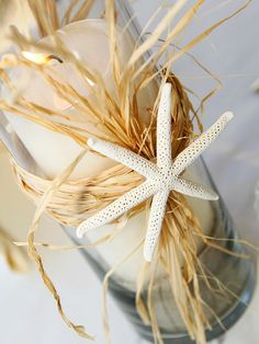 Easy-to-Make Centerpiece idea for a beach-theme wedding. See more of this wedding: http://www.bhg.com/wedding/real/real-weddings-a-do-it-yourself-beach-theme-wedding/?socsrc=bhgpin081312DIYseashellcenterpiece#page=16
