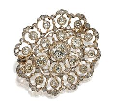 18 KARAT GOLD AND DIAMOND BROOCH, BUCCELLATI Of oval shape and openwork floral design, set in the center with an old-mine diamond weighing approximately 1.25 carats, surrounded by 18 old-mine diamonds weighing approximately 2.75 carats, mounted in 18 karat white and yellow gold, signed Buccellati.