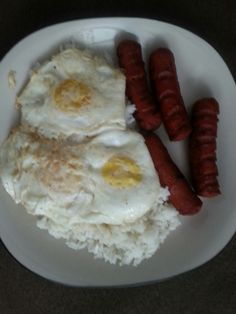 2 Hebrew International Beef hotdogs sliced with  3 Over easy Eggs on top of Rice.