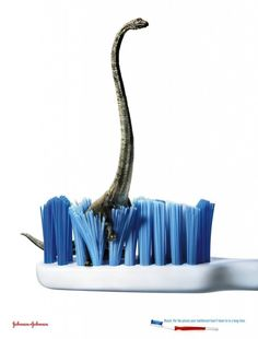 """This Johnson n Johnson poster encourages people to """"Reach. For the places your toothbrush hasn't been to in a long time."""" The artist expresses this by placing a dinosaur which represents the prolonged amount of time the user hasn't brushed their teeth properly in."""