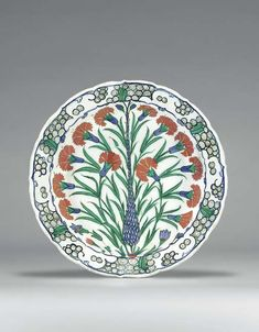 """AN IZNIK POTTERY DISH OTTOMAN TURKEY, CIRCA 1570 With cusped sloping rim on short foot, white interior painted in green, blue, red & black, slender central cypress tree issuing two small tulips, within bold floral spray of red carnations radiating from central red spot at the base of the tree, tree flanked by an asymmetric pair of carnations, with other small flowers around its base, border with blue & green stylized wave & rock, exterior with alternating blue & green paired tulips 11¾"""" diam"""