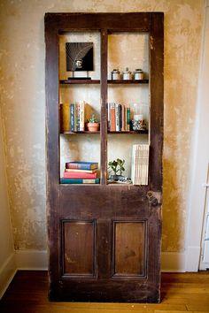vintage door repurposed into bookshelf... maybe hinge it and have storage behind the bottom of the door too!