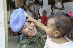 A United Nations Transitional Administration in East Timor (UNTAET) peacekeeper plays with a young child in Hera. 2/Mar/2000. Hera, East Timor. UN Photo/Eskinder Debebe.