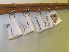 Smart way to make hangers on your dry erase board.   These are hung on the chalk tray with shower-curtain hooks for easy access.