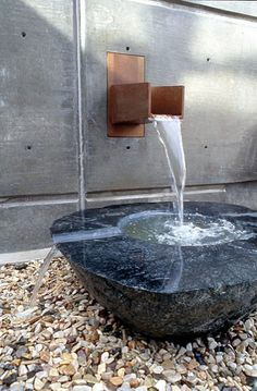 Gloria Bornstein. Recharge Chambers, 2003. Stone, bronze, water. Courtyard. King County Public Art Collection. Visitors passing through see and hear collected rainwater splashing into a black granite basin resting upon river stones, which in turn drains back into the Cedar River Aquifer. A series of four scuppers that channel rainwater from the building to the meadow below.