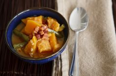 The Ivory Hut: Squash and Green Beans in Coconut Milk (Kalabasa at Sitaw sa Gata)  8 oz. bacon, diced 1 small onion, diced 4 large cloves garlic, minced 2 tablespoons fish sauce, or to taste 13.5 oz. can of coconut milk whole fresh green chilies (optional) 2 pounds squash cubes (about 1.5″ cubes, peeled) 3/4 pound long beans or green beans
