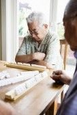 Asian_elderly : Two elderly men sitting at table playing game