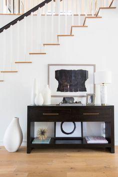 Decoração simples com contraste de cores e utilização de quadros e vasos para compor o espaço.