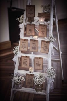 Ladder seating plan. Shabby chic, lace, gypsophila and tealights. A great way to show guests to their table.