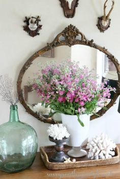 Eclectic mix - coral, bottle, flowers, mirror, and hunting trophies