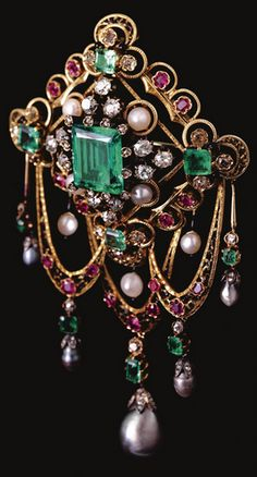 GEM-SET AND ENAMEL DEVANT DE CORSAGE , LAST QUARTER OF 19TH CENTURY Set with a step-cut emerald within pearls and circular-cut and cushion-shaped diamond clusters, further embellished by a black enamel frame, to the scrolling border of pink sapphire and circular-cut stones, suspending three articulated swags accented with pearls drops set en pampille,