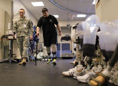 1st Sgt. Mike Leonard works with his Physical Therapy Technician Spc. Nick Peterson at Walter Reed Army Medical Center.