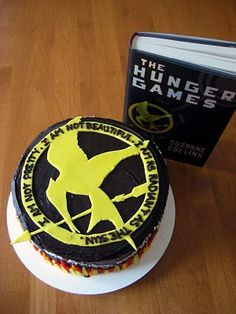 "I was thinking of making a Hunger Games themed cake for my little brother-in-law for his up-coming birthday.  I was thinking a round black (chocolate) cake with the Mockingjay pin in fondant with flames on the side.  I googled ""Hunger Games cake"" and this appeared!  Haha!  Great minds think alike.  However, I'd leave the quote off.  I think simple is more clean looking."