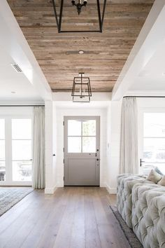 Modern Farmhouse Gray Glass Panel Door with Iron Lanterns Hanging from a Plank Ceiling Over a Gorgeous Wood Floor. Modern Farmhouse Gray Glass Panel Door with Iron Lanterns Hanging from a Plank Ceiling Over a Gorgeous Wood Floor. Interior Modern, Interior Design, Modern Decor, Modern Foyer, Interior Trim, Scandinavian Interior, Hallway Designs, Hallway Ideas, Entry Way Design