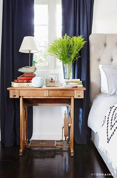 Bedroom nightstand with curated books and green plant