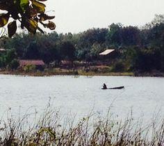 Fisherman on bamboo raft on the Lake near Nikom Kom Soi, Thailand.