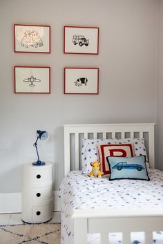 Kids room dressed with Jonathan Adler cushions & prints in red frames