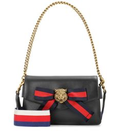 Gucci - Broadway leather shoulder bag - Gucci's Broadway shoulder bag is an oh-so-covetable addition to the designer's line. The envelope-style structured silhouette is crafted from smooth black leather and given a signature twist with a ribbon bow in the designer's navy and red stripes and antique gold-tone lion head hardware. A thick, striped shoulder strap can be used for hands-free days. seen @ www.mytheresa.com