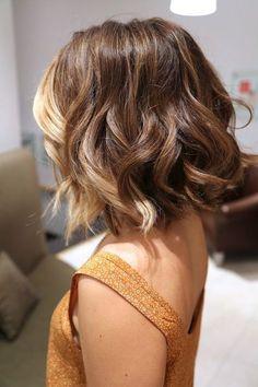 Les ondulations réalisées dans cette coupe au carré donnent un beau volume aux cheveux de cette jeune femme. On peut aussi remarquer la coloration blonde dans les cheveux du devant. Le reste de la chevelure est châtain.