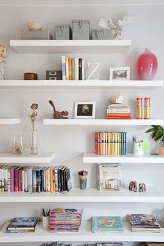 Gold & Gray blog. Staggered white floating shelves. Love the lean lines and punches of color.