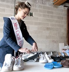 Miss Cache Valley Morgan Flandro sorts through shoes in North Logan, Utah. Miss Cache Valley winners have collected thousands of shoes which will benefit areas in Africa. (Photo by John Zsiray)