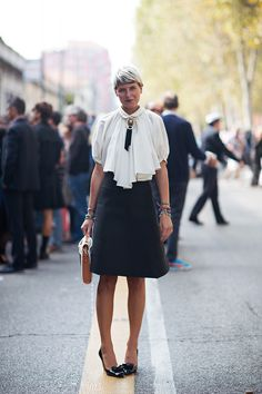 Elisa Nalin in a flare skirt, billowy blouse, flower cameo brooch, and black pumps.