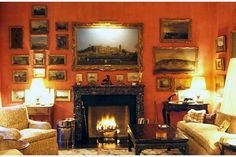 Paul Mellon's study at the couple's townhouse in New York City, decorated with the help of several interior designers, including John Fowler, Paul Leonard, Billy Baldwin, and Bruce Budd. Gilt-framed antique landscapes fill the walls, which have been painted a rich coral.