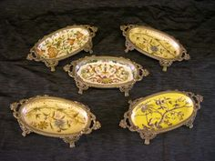 Collection of Five Vanity Trays, consisting of a pair of Chinese brass-mounted elliptical porcelain vanity trays in floral decor, a similarly mounted Chinese porcelain vanity tray decorated with mulberry flowers on an Imperial Yellow craqueléur ground, a similar vanity tray in mulberry, celery green and ochre Birds and Branches decor and a fifth vanity tray of like form, similarly mounted, in India Flowers