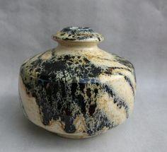 Praktvase i keramikk, signert Hanne Havrevold, som var gift med Eirik Pløen. Dette er en praktvase som går i beige, sort og gult, med en utsøkt form. Det gule blir mer fremtredende i sterkt lys.