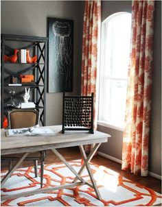 Chic orange office design with gray wall paint color, white tufted slipper chair, black accent table, white & orange curtains, rustic sawhorse desk and Coral Arabesque Rug. Orange Office, Decor, Interior Design, House Interior, Home, Rustic Home Offices, Contemporary House, Orange Curtains, Home Decor