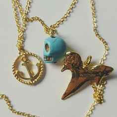 Three layer anchor skull shark tooth necklace Adorable gold three teired layered necklace with three charms from a circle that looks like rope surrounding an anchor a blue natrual turquoise skull and a gold shark tooth. Very cool and a great accessory for your favorite jeans and t shirt. Jewelry Necklaces