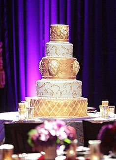 The gold-and-ivory wedding cake by Rosebud Cakes brings out the gold accents in the @Mandy Dewey Seasons Hotel Westlake Village décor.