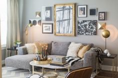 Living room features gray walls adorned with a black,white and gold gallery wall over a modern gray sofa with chaise lounge layered with Mongolian wool and gold silk pillows along with a black and white striped throw.The gray sectional is flanked by a pair of coffee tables. silver decor