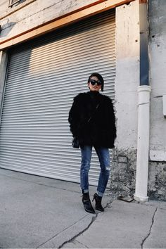 Olivia Lopez of Lust for Life wears a fur coat, Chanel bag, cuffed jeans, and black boots