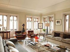 Las butacas de los años 50, los sofás de estilo contemporáneo, y una mesa vintage crean un acogedor estilo ecléctico