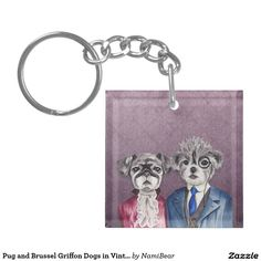 Keychain. This is a watercolor painting of a pug and a mix of brussel griffon and poodle dogs wearing vintage clothing. The pug is wearing a dark purple or magenta dress with a lace scarf and pearls. The brussel griffon is wearing a dark blue and grey vest suit. He's also wearing a monocle.