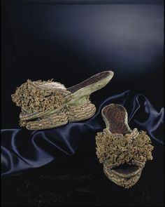 Shoes of this type are called chopines or pantobles. The design was based on shoes worn in Turkish baths. They were originally a type of overshoe, which is why they have no back. People wore later versions either as overshoes or on their own.   This delicate and elegant pair of chopines are made of wood covered with silk velvet and trimmed with silk ribbon and gold lace. The upper is divided with holes for lacing. Venice, circa 1600, wood, velvet, leather, silver gilt braid, bobbin lace