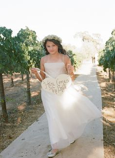 Sunstone Villa wedding ceremony. Flower girl holding Here Comes the Bride sign walking in vineyard down the aisle. Photography: Erin Leigh - www.thebowerygirl.com  Read More: http://www.stylemepretty.com/california-weddings/2014/04/01/romantic-vintage-wedding/