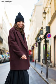 Street Style portraits by Ángel Robles. Fashion Photography from Paris Fashion Week. Woman smoking on the street, wearing oxblood coat, maxi pleated skirt and black beanie, Paris.